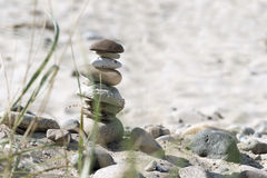 Stone tower and  plants on a sandy beach, vacation background Stock Photos