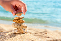 Stone tower on sand with hand. Royalty Free Stock Image