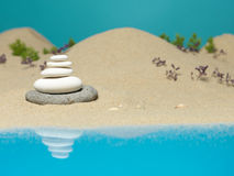 Stone tower in sea shore miniature background. Zen therapy stone tower, on a sea shore miniature landscape, with reflexions in the sea Stock Image