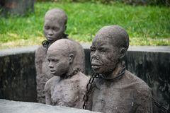 Slavery monument near the former slave trade place in Stone town, Zanzibar. STONE TOWN, ZANZIBAR - JAN 3, 2018: Slavery monument with sculptures and chains near royalty free stock images