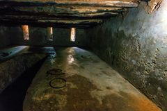 STONE TOWN, ZANZIBAR - JANUARY 9, 2015: Inside cell for slaves. STONE TOWN, ZANZIBAR - JANUARY 9, 2015: Inside stone cell for slaves with old metal fetters on Stock Images