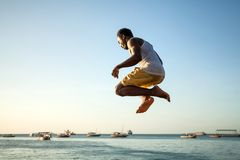 Man diving off seafront wall into sea. royalty free stock photo
