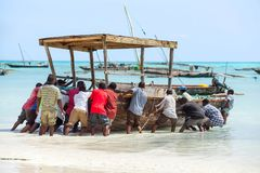 Men pushing fishing boat into the sea. royalty free stock photography
