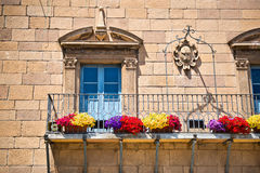 Stone townhouse with Art Nouveau windows. With carved architraves above colorful flower boxes attached to the iron railing on the exterior balcony, Poble Royalty Free Stock Photography