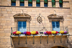 Stone townhouse with colorful flower boxes. Attached to the iron railing on the exterior balcony below Art Nouveau style windows with carved architraves, Poble Royalty Free Stock Image