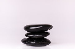 Stone treatment. Black massaging stones  on a white background. Hot stones. Balance. Zen like concepts. Basalt stones. Stock Images