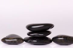 Stone treatment. Black massaging stones  on a white background. Hot stones. Balance. Zen like concepts. Basalt stones. Stone treatment. Black massaging stones Royalty Free Stock Photography