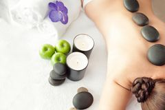 Stone treatment. Top view of beautiful young woman lying on fron. T with spa stones on her back.  Beauty treatment concept Royalty Free Stock Photos