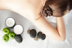 Stone treatment. Top view of beautiful young woman lying on fron. T with spa stones on her back.  Beauty treatment concept Stock Image