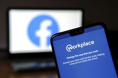 Workplace app on the smartphone and blurred Facebook logo on the background. Workplace is