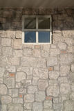 Stone veneer wall with window. In daylight Royalty Free Stock Images