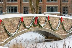 Stone walk bridge over pond in winter. Stone bridge over stream decorated for the holidays with wreath and garland Stock Photography