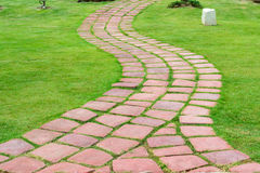 Stone walk path in the park. With green grass Royalty Free Stock Photos