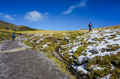 Stone walk way with ice and snow mountain and people trekking Royalty Free Stock Images