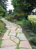 Stone Walking Trail Through Flower Beds. A shale walkway winds through flowerbeds, toward a little building. Trees overhang the flowers and grass grows between Stock Photos