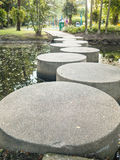 Stone walkway across the river in the park. Stock Image