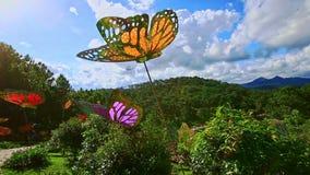 Stone Walkway among Big Butterflies Sculptures in Tropical Park stock video