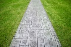 Stone walkway on a grassy in the park Royalty Free Stock Photography