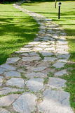 Stone walkway in the park. With green grass Royalty Free Stock Photos