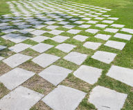 Stone walkway pattern on a grass field in perspective view Stock Image