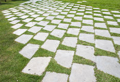 Stone walkway pattern on a grass field in perspective view Stock Photo