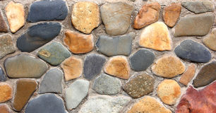 Stone wall. Of the house from different color of stones in a laying Stock Photos