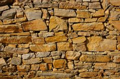 Stone wall. Old orange wall combined manually from non-uniform stones Royalty Free Stock Images