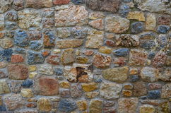 Stone wall. Wet red blue gray built stone wall Royalty Free Stock Photo
