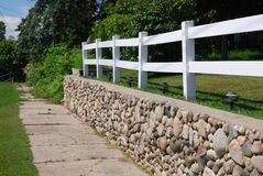 Stone Wall. A stone wall along the sidewalk with a white fence Stock Photo