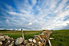 Stone Wall. Rural scene from Co.Sligo, Ireland shows stone wall topped with barbed wire fence Royalty Free Stock Photos