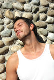 Stone wall. Beauty man while tanning on the stoned wall royalty free stock photography