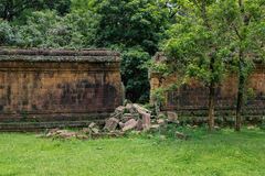 A stone wall of an ancient ruin with a big gap from a break through - angkor Stock Photography