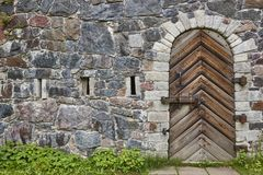 Stone wall with antique castle locked wooden door. Vintage Stock Photos
