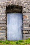 Stone wall with arch and metal door Stock Images