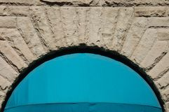 Stone Wall Arch w/ Blue Awning in Portland, OR. This is a blue awning set within an arched window in a stone building wall in Portland, OR Stock Photo