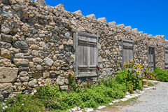 Stone wall with arched wooden door Stock Photo