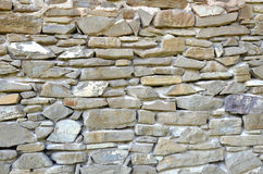 Stone wall as a part of old rural farm building, close-up.  Stock Photo