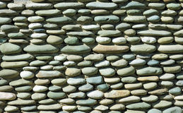Stone wall background. Old wall made of round stones royalty free stock image