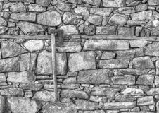Stone wall background and axe in black and white Royalty Free Stock Photography