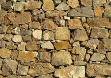 Stone wall background. Background of stone wall of boulders and pebbles. Stock Photo