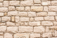 Stone wall. Background of stone wall built with irregular sized stones with the joints filled with matching lime mortar Stock Photo