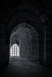 Stone wall with a backlit window with iron grid at an old citadel in Alexandria, Egypt Stock Photography