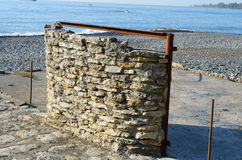 Stone wall on the beach Stock Images
