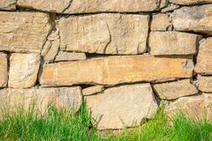 Stone wall behind a grass lawn stock image