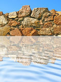 Stone wall being reflected in ripple blue water. Stock Images
