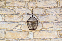 Stone wall with bird cage. Old bird cage hanging over old stone wall Royalty Free Stock Image