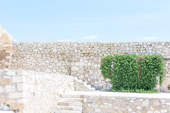 Stone wall and blue sky with clouds, background free space for text Stock Photos