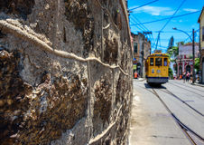 The stone wall, blue sky and old-fashioned yellow tram in Santa Royalty Free Stock Photo