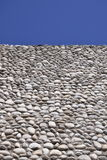 Stone wall and blue sky. A perspective style background photograph of a stone wall topped by a bright blue sky stock photo