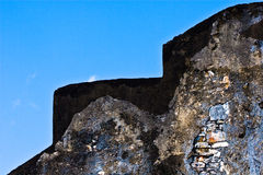 Stone wall and blue sky. Section of a wall in trinidad showing exposed stone Royalty Free Stock Photography